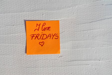 Handwriting text on memo post reminder. I love Fridays on paper, on white and textured wall.  Copy space.