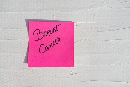 Handwriting text on memo post reminder. Breast Cancer on paper, on white and textured wall.  Copy space.