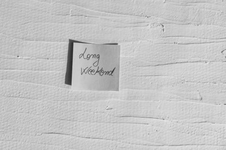Handwriting text on memo post reminder. Long weekend on paper, on white and textured wall.  Copy space.