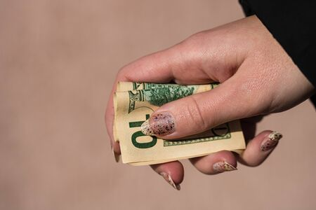 Hands giving money like a bribe or tips. Holding US dollars banknotes on a blurred background, US currency Stok Fotoğraf