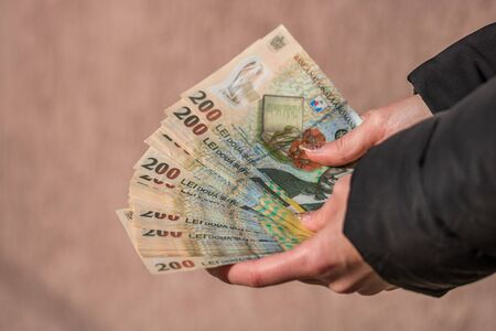Woman hand giving money like bribe or tips isolated. LEI currency banknotes close up. Reward for hard work, finance and business concept Stok Fotoğraf