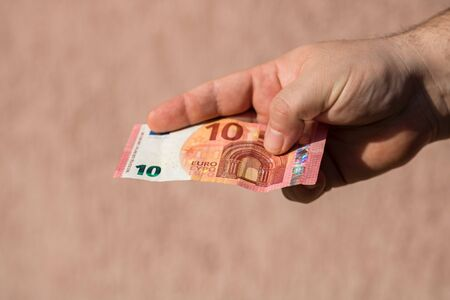 Man hands giving money like a bribe or tips. Holding EURO banknotes on a blurred background, EU currency