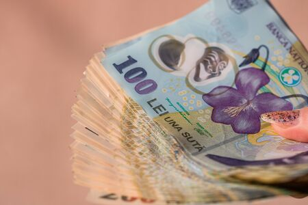 Woman hand giving money like bribe or tips isolated . LEI currency banknotes close up. Reward for hard work, finance and business concept