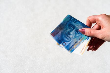 Woman hand holding and giving money. World money concept, close up of 100 swiss franc banknote, photo of CHF currency isolated. Hand holding money, swiss franc