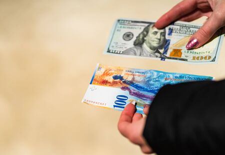 Woman hand holding and giving money. World money concept, close up of 100 swiss franc banknote and 100 US dollar, photo of CHF and USD currency Stock fotó - 140234616