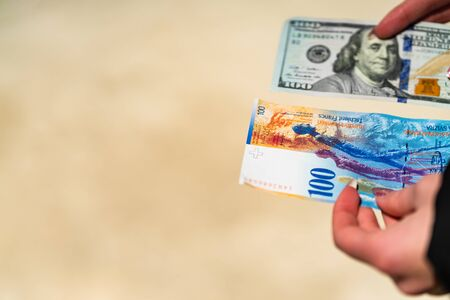 Woman hand holding and giving money. World money concept, close up of 100 swiss franc banknote and 100 US dollar, photo of CHF and USD currency Stock fotó - 140234617