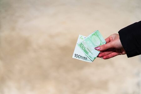 Woman hand holding and giving money. World money concept, close up of 100 EURO banknote, photo of EUR currency isolated. Hand holding money, EURO currency