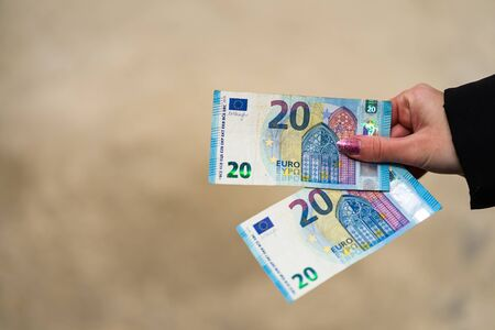 Woman hand holding or giving money like a bribe or tips. World money concept, close up of 20 EURO banknote, photo of EUR currency isolated. Hand holding money, EURO currency