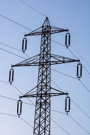 High voltage post. High voltage tower on blue, clear sky.
