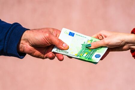 Hand giving money like bribe or tips or salary isolated, hard worked hand taking euro banknotes. Currency transfer and reward for hard work. Stock fotó