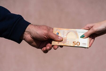 Hand giving money like bribe or tips or salary isolated, hard worked hand taking euro banknotes. Currency transfer and reward for hard work.
