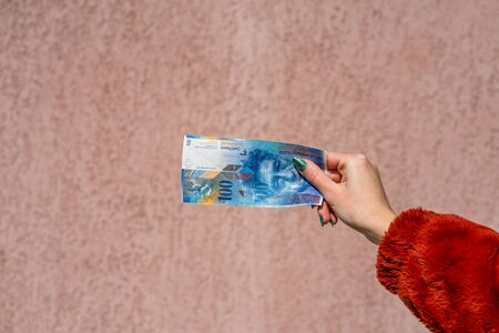 Hand holding showing euro money and giving or receiving money like tips, salary. 100 swiss franc banknotes CHF currency isolated. Concept of rich business people, saving or spending money.
