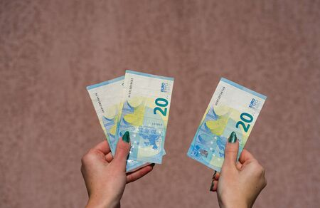 Hand holding showing euro money and giving or receiving money like tips, salary. 20 EURO banknotes EUR currency isolated. Concept of rich business people, saving or spending money.
