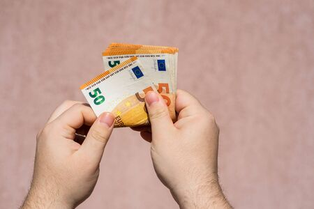 Hand couting holding and showing euro money or giving money. World money concept, 50 EURO banknotes EUR currency isolated with copy space. Concept of rich business people, saving or spending money.