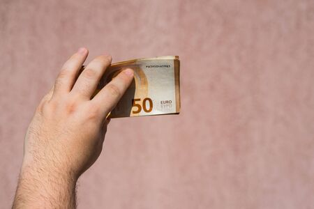Hand holding showing euro money and giving or receiving money like tips, salary. 50 EURO banknotes EUR currency isolated. Concept of rich business people, saving or spending money.