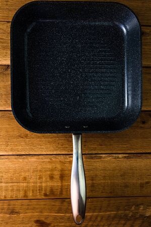 Black frying pan, grill over wooden table, top view, copy space, barbeque concept