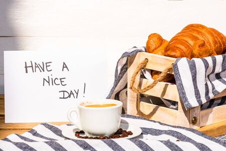"""Coffee cup and buttered fresh French croissant on wooden crate. Food and breakfast concept. Morning message """"have a nice day"""" on white board"""