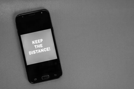 Keep the distance text on the screen of a smartphone. Medical protective equipment isolated. Flu disease virus spreading, virus protection methods. Stock Photo