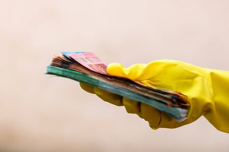 World money concept, hand with gloves receiving, giving or holding EURO banknote, isolated on blurred background. Corona virus COVID-19 outbreak. Concept of prevention virus spread