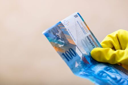 World money concept, hand with gloves receiving, giving or holding 100 swiss franc banknote, isolated on blurred background. Corona virus COVID-19 outbreak. Concept of prevention virus spread Stock Photo