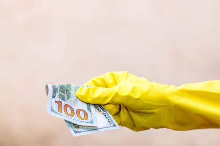 World money concept, hand with gloves receiving, giving or holding 100 USD banknote, isolated on blurred background. Corona virus COVID-19 outbreak. Concept of prevention virus spread