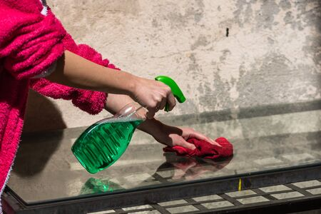 Woman cleaning glass table red microfiber rug and cleaning sprayer, cleaning services concept. Housework and housekeeping concept