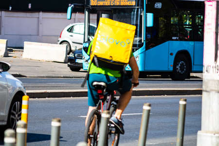 A Glovo food delivery courier on a bike. Restaurants are closed and only deliveries are allowed during the state of emergency due to coronavirus COVID-19 outbreak in Bucharest, Romania, 2020