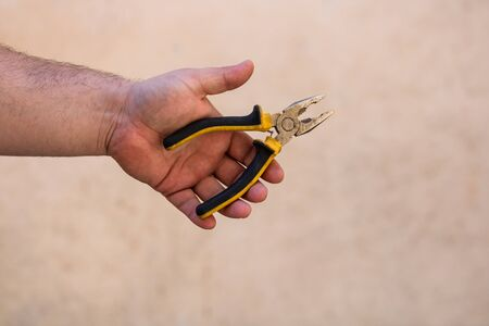 Tools for repair and building. Hand holding pliers on blurred background