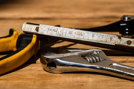 Tools for repair and building. Hummer, adjustable spanner, ruler. Instruments on rustic wooden table with copy space