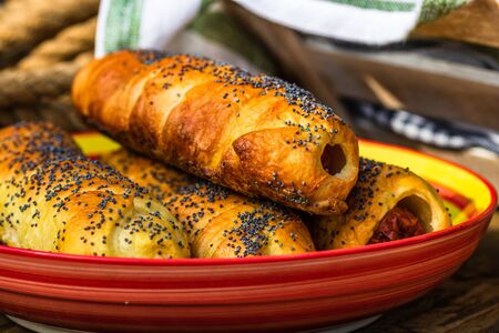 Sausages baked in dough sprinkled with salt and poppy seeds in a rustic composition. Sausages rolls, delicious homemade pastries.