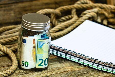 Composition with saving money banknotes in a glass jar with spiral notebook. Concept of investing and keeping money for business, close up isolated.
