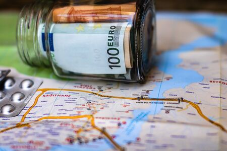 Composition with saving money banknotes in a glass jar with pills on map. Concept of investing and keeping money for healthcare and travel, close up isolated. Фото со стока