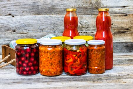 Jars with variety of canned vegetables and fruits, jars with zacusca and bottles with tomatoes sauce. Preserved food concept in a rustic composition.