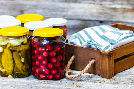 Jars with variety of canned vegetables and fruits, jars with zacusca. Preserved food concept in a rustic composition. Banco de Imagens