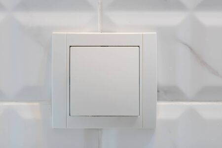 Close up view of white electric light switch on white tile. Building construction elements concept, interior design. 版權商用圖片