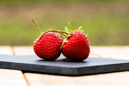 Close up of two strawberries on small black cutting board isolated outdoor on wooden table. Banque d'images