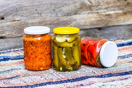 Glass jars with pickled red bell peppers and pickled cucumbers (pickles) isolated. Jars with variety of pickled and canned vegetables. Preserved food concept in a rustic composition.