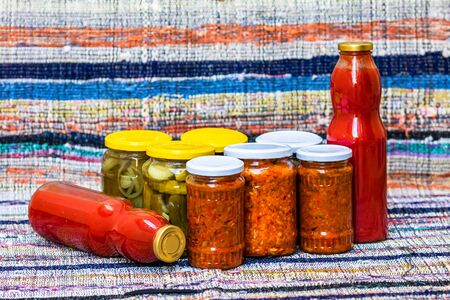 Glass jars with pickled red bell peppers and pickled cucumbers (pickles) isolated. Jars with variety of pickled vegetables, jars with zacusca and bottles with tomatoes sauce. Preserved food concept. Banco de Imagens