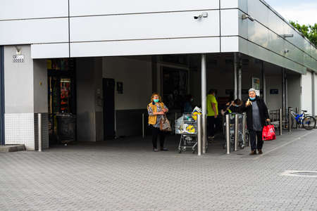 People wearing surgical mask at the entrance of LIDL supermarket in Bucharest, Romania, 2020