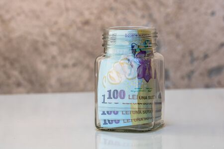 Composition with saving money romanian LEI banknotes in a glass jar. Concept of investing and keeping money, close up isolated. Archivio Fotografico