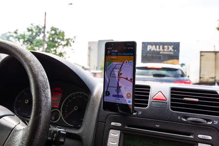 Using waze maps application on smartphone on car dashboard, Driver using maps app for showing the right route through the traffic of city on a rainy evening. Bucharest, Romania, 2020.