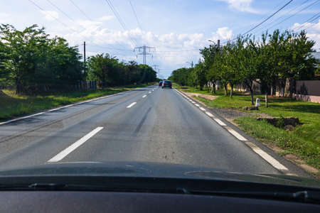 Traffic on sunny day with road view through car front window in a village near Bucharest, Romania, 2020