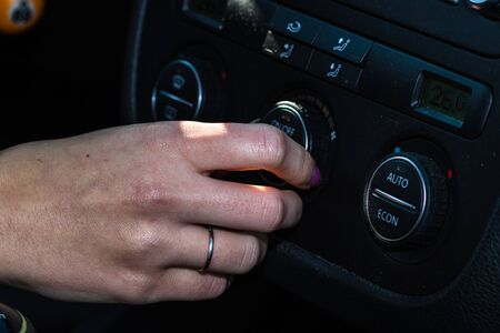 Driver`s hand using control buttons of modern car. Woman adjusting air conditioning in car. Stock Photo