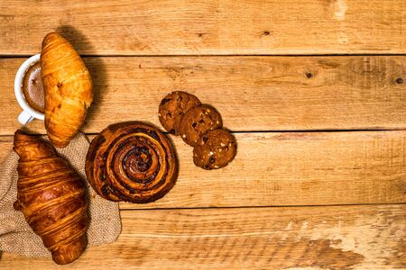 Fresh croissant and biscuits on wooden table. Coffee, food and breakfast concept. Desserts, fresh pastries and coffee. Top view and copy space