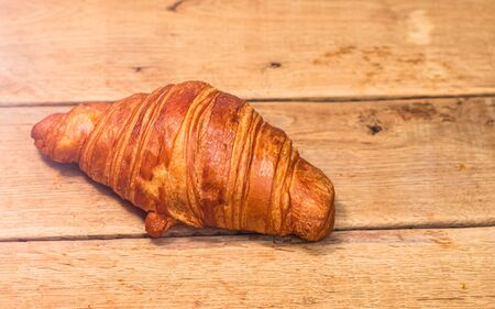Detail of fresh croissant on wooden table. Food and breakfast concept. Top view and copy space Stock Photo