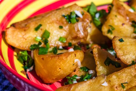 Close up with selective focus of fried potatoes with green onion, green garlic and spices in a colorful plate.