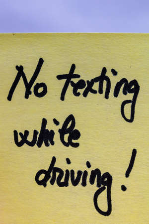 No texting while driving handwriting text close up isolated on yellow paper with copy space. Stock Photo