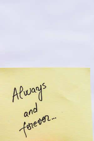 Always and forever handwriting text close up isolated on yellow paper with copy space.