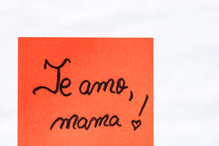 Te amo mama (I love you mom) handwriting text close up isolated on orange paper with copy space. Writing text on memo post reminder