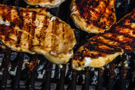 Chicken and pork steak grilled on a charcoal barbeque. Top view of camping tasty barbecue, food concept, food on grill and detail of food on the grill
